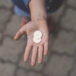 Main ouverte avec 2 pièces d'argent dans la paume.